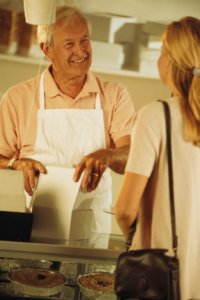 A Recipe for Success with your Start Up Food Business - image - man wearing apron serves woman in shop