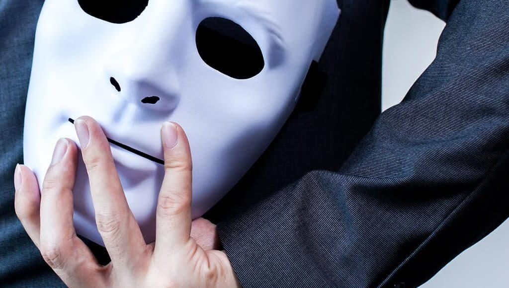 Understanding Identity Fraud: How to Protect your Company Directors image - man wearing dark clothing hiding a white mask behind his back
