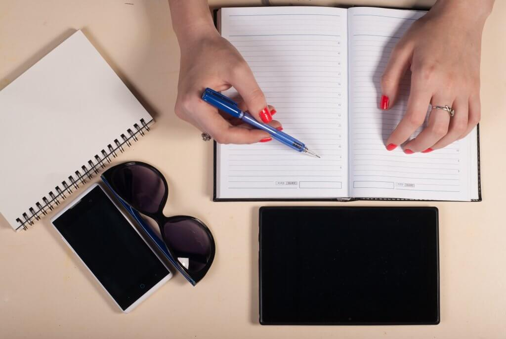 Start-Up Efficiency: 6 of the best free apps for a productive day. Photo - Woman writing in diary with a tablet, sunglasses and another notebook